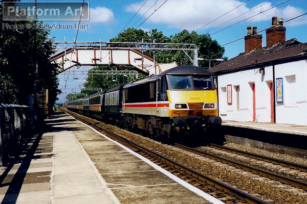 In Inter City Mainline livery, Class 90 90029 passes Penkridge in Staffordshire on 8th July 1990 with a southbound inter-regional express.