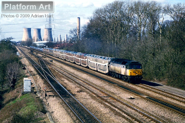 Railfreight liveried Class 47 47379 is seen on the up relief line east of Didcot on 26th March 1999 with the late running 6O95 09.52 Washwood Heath - Dollands Moor Rover car train.