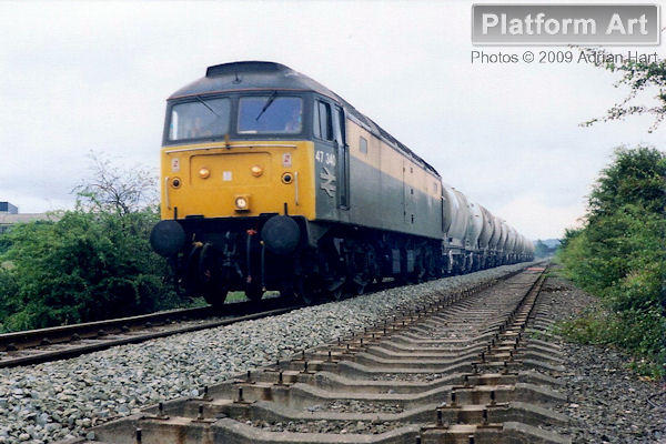 Civil Engineer liveried Class 47 locomotive 47340 powers the 6M26 15.25 Earles Sidings - Handsworth cement train past Hazel Grove on 19th July 1991. This section of line between New Mills and Cheadle Heath is used exclusively by freight services.