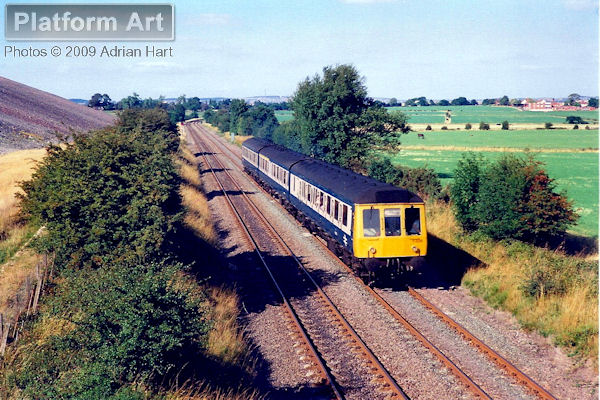Tyseley based Class 117 DMU set T309 passes Essington on 3th September 1990 with a local service between Cannock and Walsall. Pye Green and Cannock Chase can be seen in the distance.