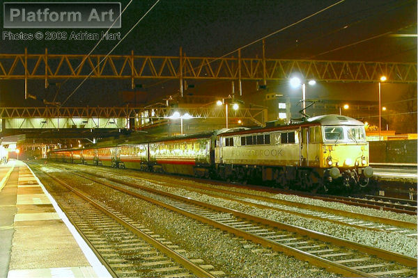 Porterbrook liveried Class 87 87002 waits at Stafford in June 2005 with a southbound express for London Euston.