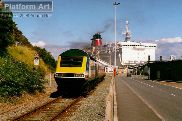 Great Western Trains HST power car 43190 leaves Fishguard Harbour on 30th August 2001 with the slightly delayed 13.55 service to London Paddington. In the background, the 14.30 Stena Line ferry to Rosslare is just departing for its three hour trip across the Irish Sea.