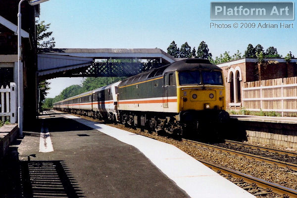 47483 hauls DVT 82151 through Codsall between Telford and Wolverhampton on 14th July 1990 with the 14.29 Shrewsbury - London Euston. The Class 47 will be replaced with electric traction at Wolverhampton for the remainder of the journey under the wires to London.