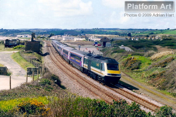 With a mix of liveries, First Great Western HST power cars 43023 and 43133 pass Marazion on 18th April 2002, shortly after leaving Penzance with the 13.45 service to London Paddington.