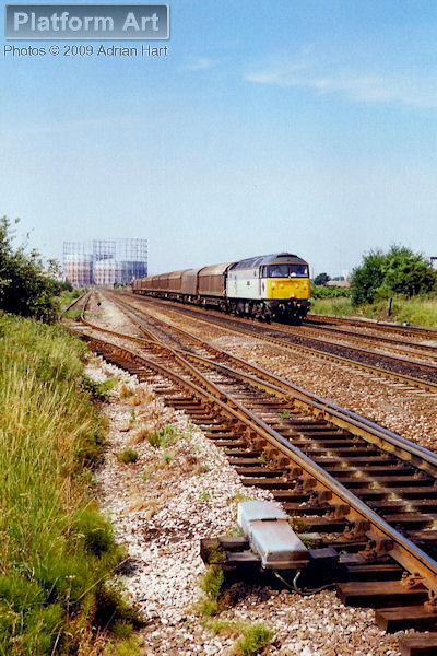 Class 47 47380 Immingham in Railfreight Petroleum livery appropriately powers the 6E48 Hallen Marsh - Immingham Norsk Hydro service, seen passing Washwood Heath in Birmingham on an almost cloudless 17th July 1990.